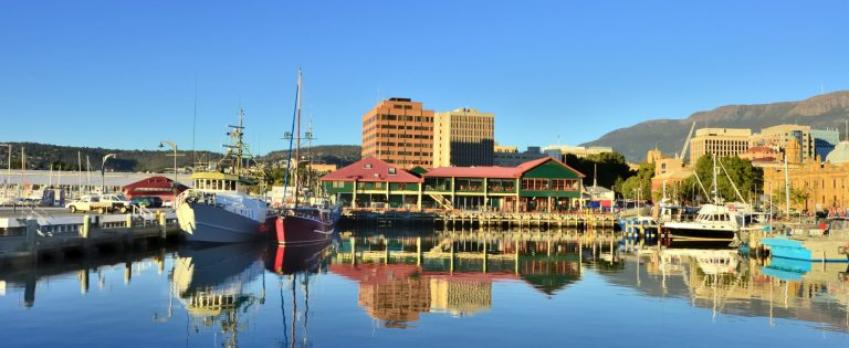 The Hobart fishing marina and city skyline with reflections of the surrounding object in the water. Mt Wellington rises in the background.
